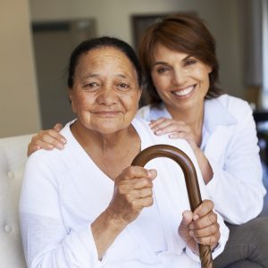 A senior woman holding a walking stick and sitting with her doctor