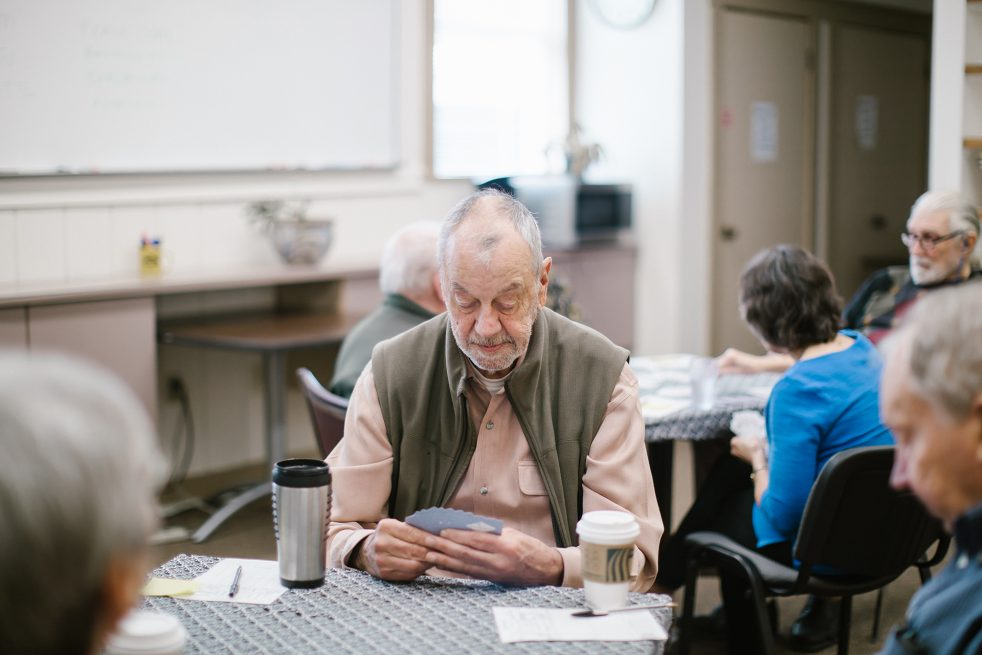older man at sno valley senior center playing cards