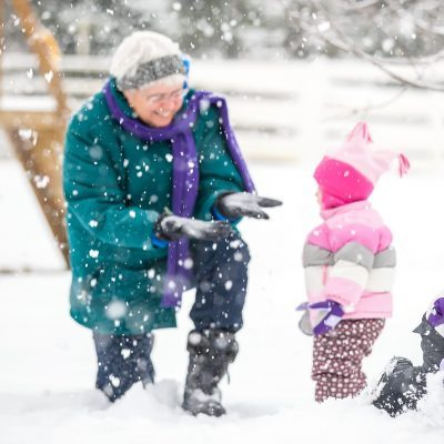 Two Young Girls Playing in Snow with Grandma