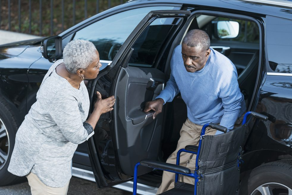 older woman helping man out of car
