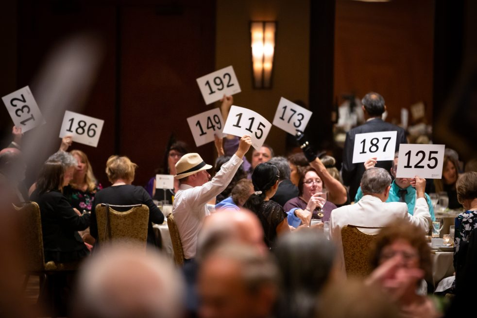 people holding bidder cards at the Golden Gala