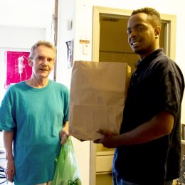 A man delivers a meal to a Meals on Wheels client