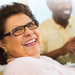 Smiling senior woman at dining table with friends