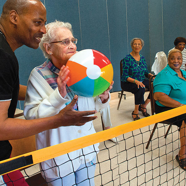 Seniors playing indoor volleyball with an activities director
