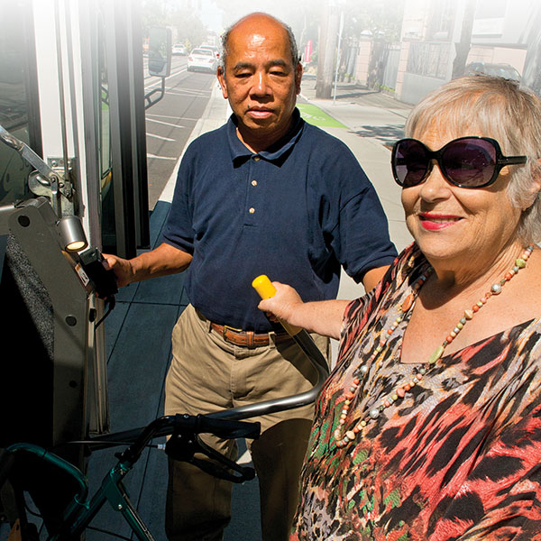 Driver helping a senior woman get into the shuttle