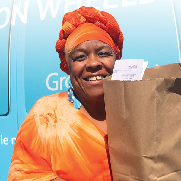 Smiling senior woman with a bag of groceries