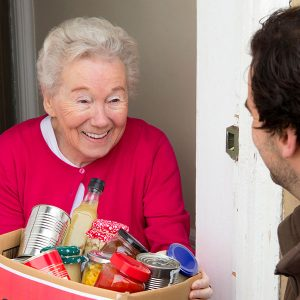 Senior woman accepting a box of canned goods at home