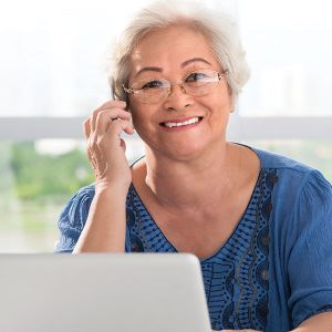 Smiling senior woman on the phone with her laptop open