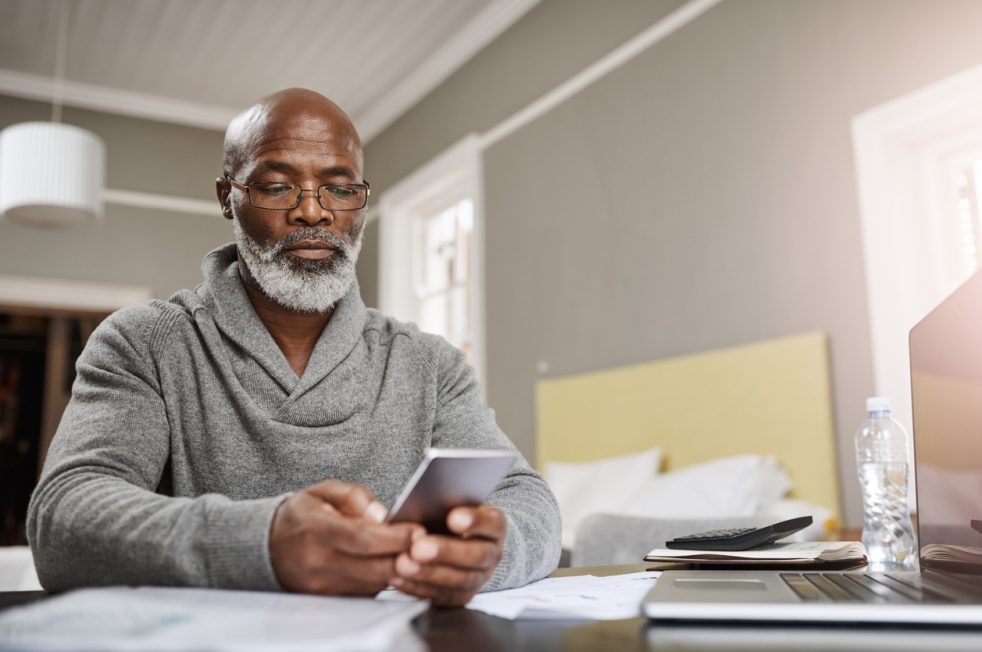 older man looking at his finances on his phone