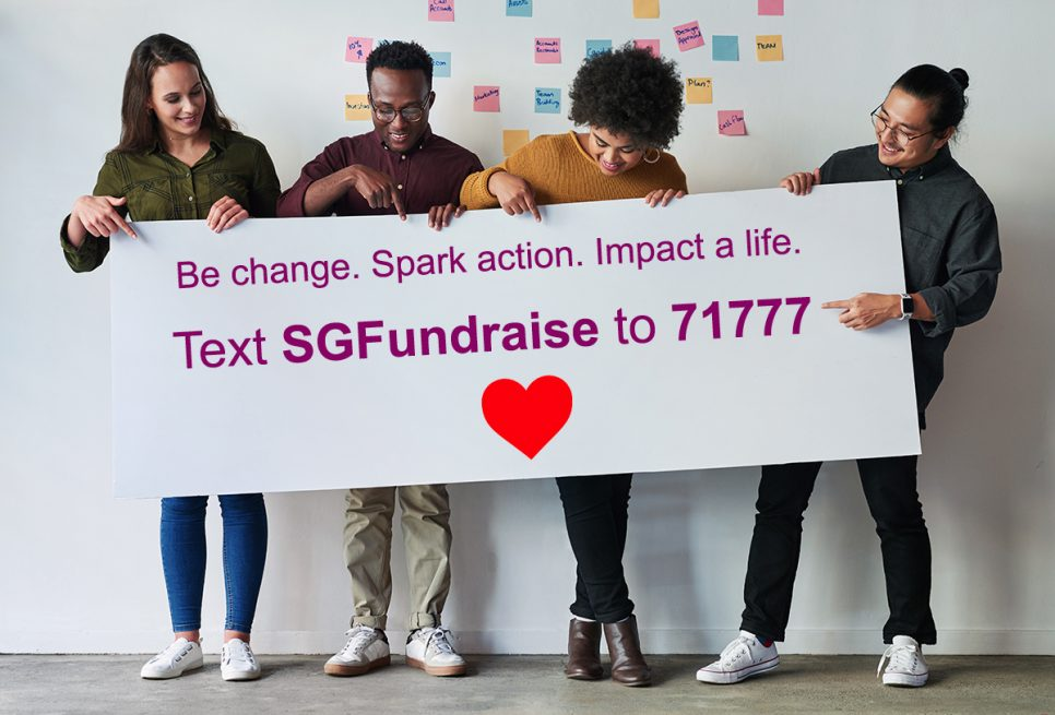 people holding a sign that says text SGFundraise to 71777