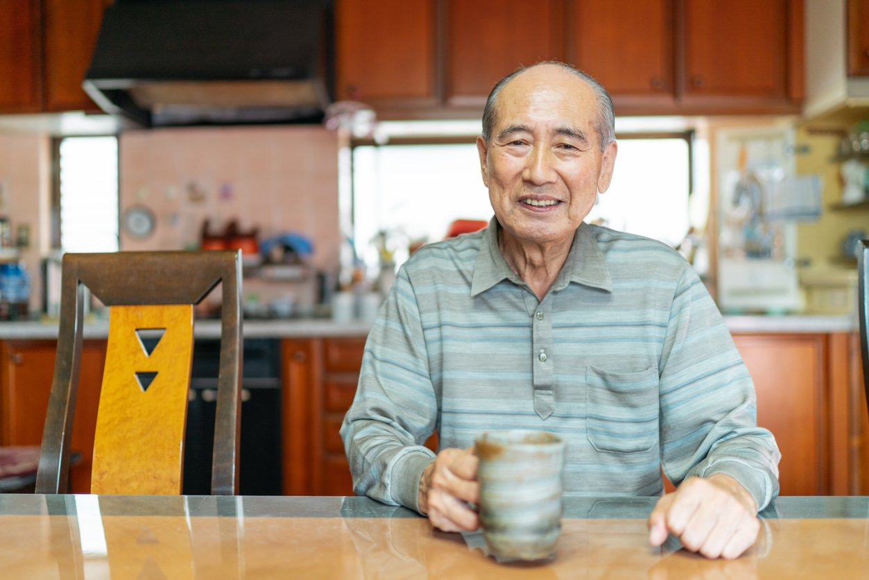 A portrait of a happy senior man while holding a coffee mug at home
