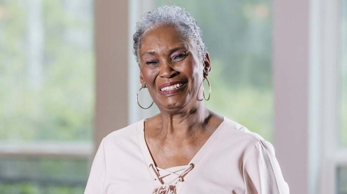Portrait of a senior African-American woman in her 70s, smiling at the camera.
