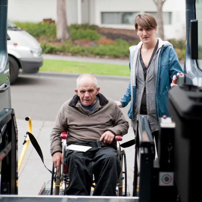 elderly man in wheelchair entering an assisted transportation vehicle
