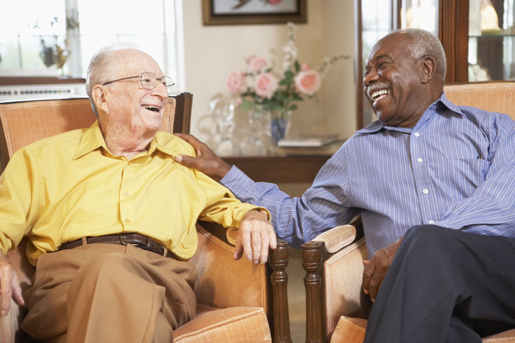 Aging men relaxing in armchairs and laughing together