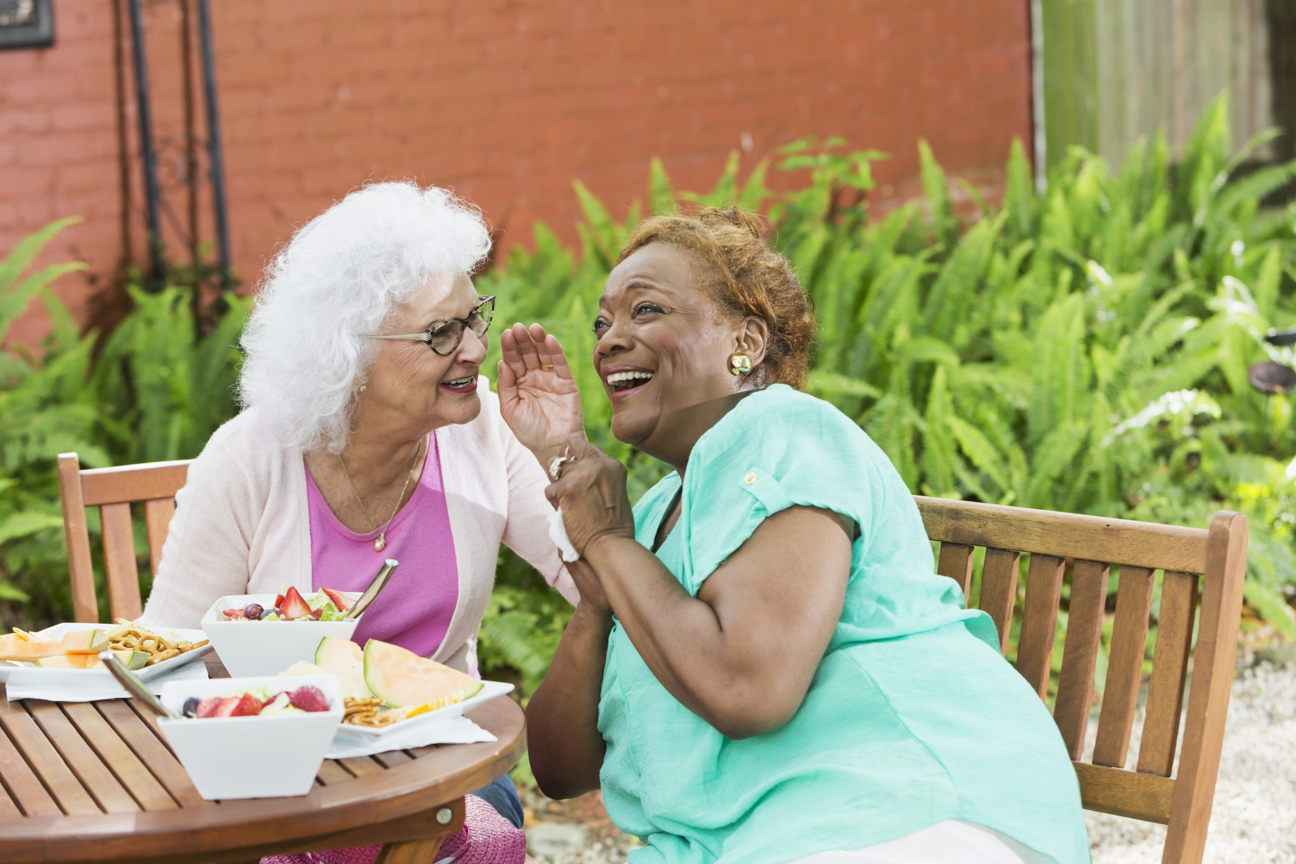 two older adults eating lunch and laughing