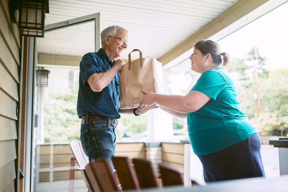 woman delivering brown bag to elderly man