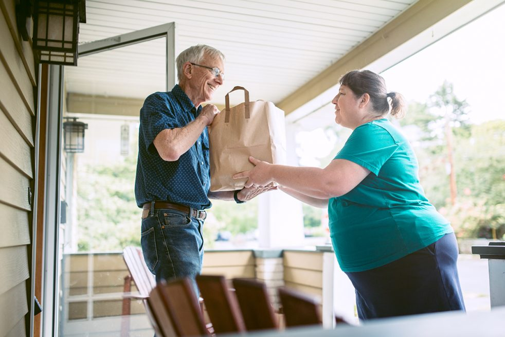 woman delivering bagged meal to a senior man