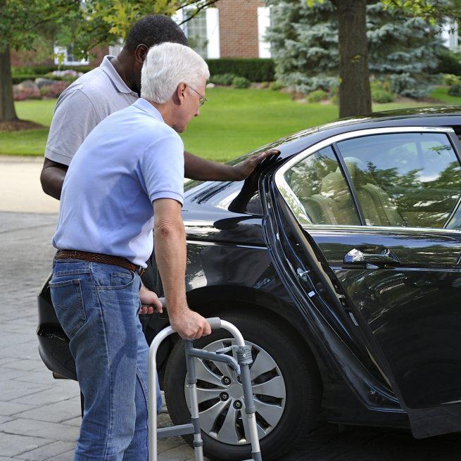 man helping older man into car
