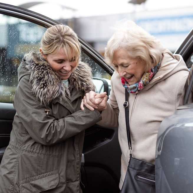 lady helping older woman out of car